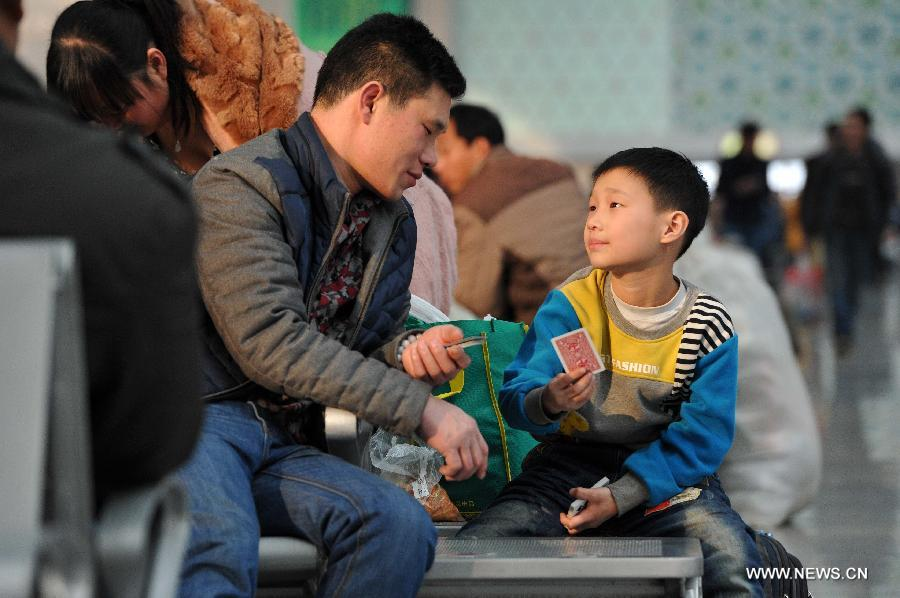 Eight-year-old Wang Chuanning plays poker with his father while waiting for their train home at the railway station of Yinchuan, capital of northwest China's Ningxia Hui Autonomous Region, Feb. 2, 2015.