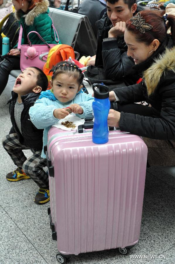 Ma Wenqiang (1st L), Ma Junli (2nd L) and their parents wait for their train home at the railway station of Yinchuan, capital of northwest China's Ningxia Hui Autonomous Region, Feb. 2, 2015.