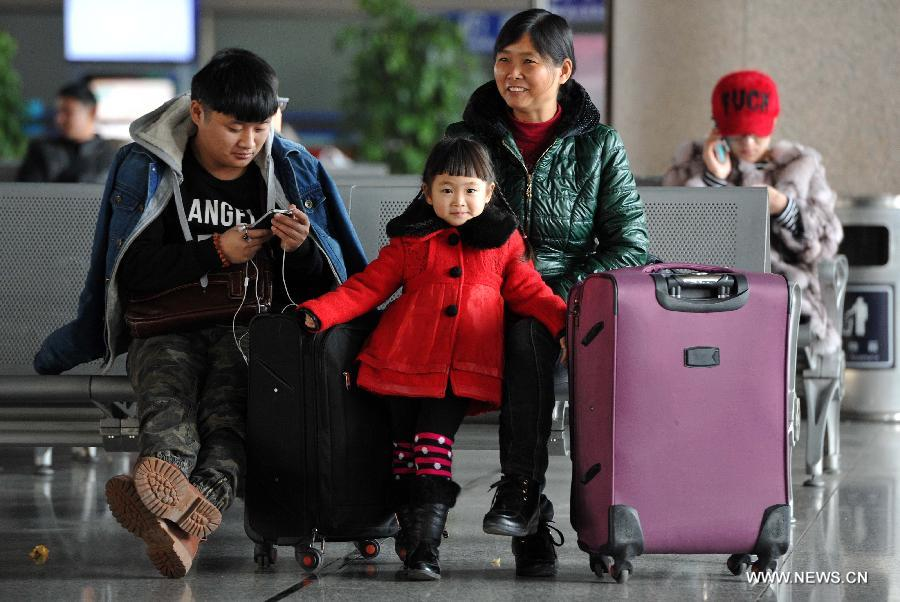 Four-year-old Wang Jiaqi (C) and her family members wait for their train home at the railway station of Yinchuan, capital of northwest China's Ningxia Hui Autonomous Region, Feb. 2, 2015.