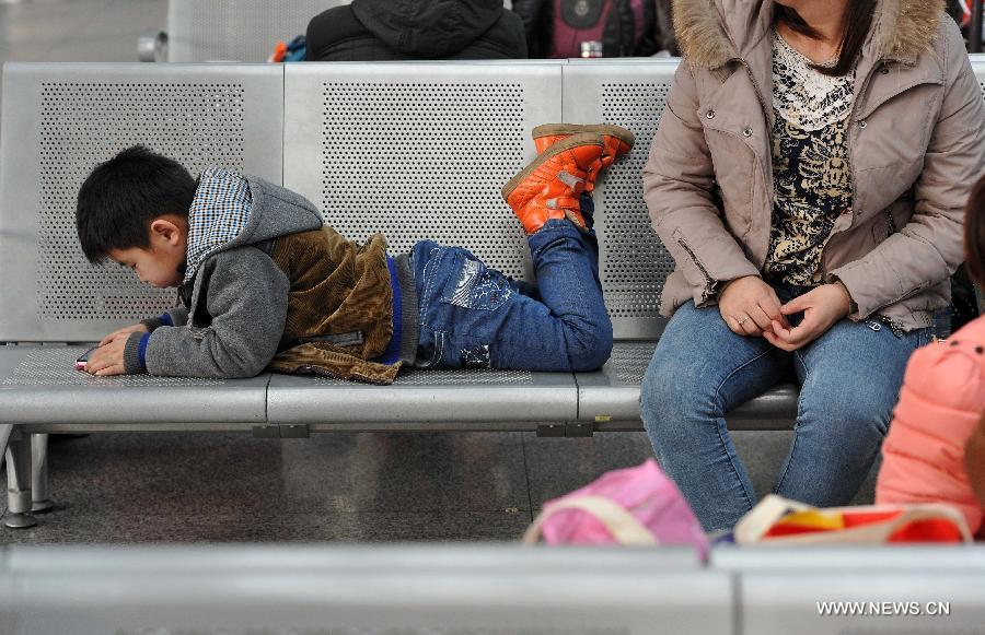 The six-year-old Liu Yuchen plays on a chair while waiting for their train home with his mother at the railway station of Yinchuan, capital of northwest China's Ningxia Hui Autonomous Region, Feb. 2, 2015.