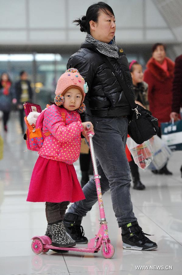 A little girl riding a scooter heads for her train home with her mother at the railway station of Yinchuan, capital of northwest China's Ningxia Hui Autonomous Region, Feb. 2, 2015.