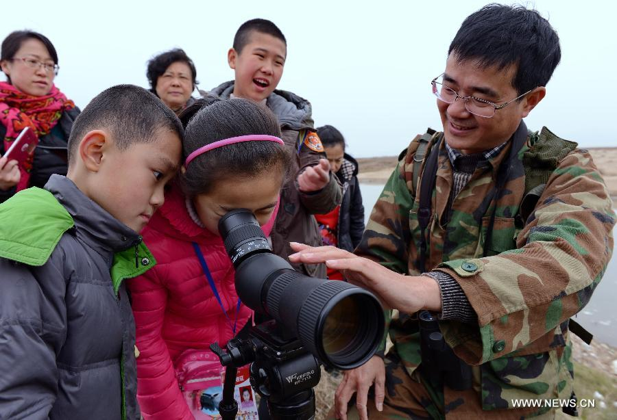 Children observe birds at Min River Estuary National Wetland Park in Changle of Fuzhou, southeast China's Fujian Province, on the occasions of World Wetland Day, on Feb. 2, 2015.