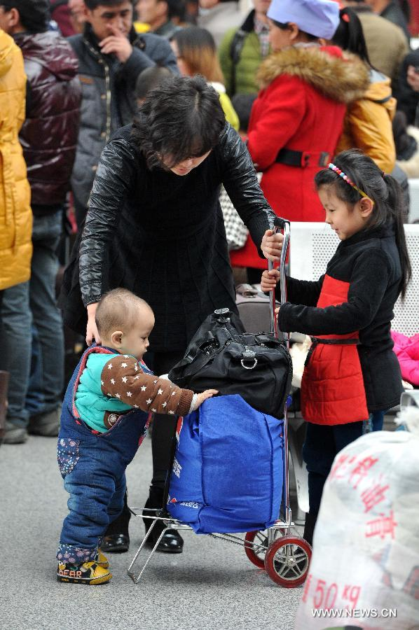 Yuan Zehao (1st L front) and his sister Yuan Zetong (1st R front) help their mother pushing their luggage at the railway station of Yinchuan, capital of northwest China's Ningxia Hui Autonomous Region, Feb. 2, 2015.