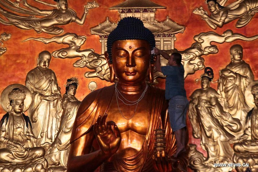 A worker cleans the statue of Buddha in preparation for the Chinese Lunar New Year celebrations inside a temple in Manila, the Philippines, Feb. 10, 2015. The Chinese Lunar New Year will be celebrated on Feb. 19. (Xinhua/Rouelle Umali)