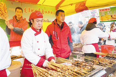 卖羊肉串摊位老板赵山(穿红衣者)。新京报记者