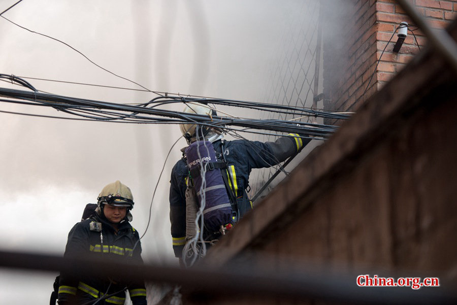Firefighters pump water into a blazing building in a residential area in downtown Beijing on Thursday, March 5, the traditional Chinese Lantern Festival. The building located between Linglong Rd. and Qixiancun Rd. in Haidian District, is used as a warehouse of Gehua, Beijing's local cable TV service provider. The burning rubber from the cable wire gives out a strong black smoke. [Photo by Chen Boyuan / China.org.cn]