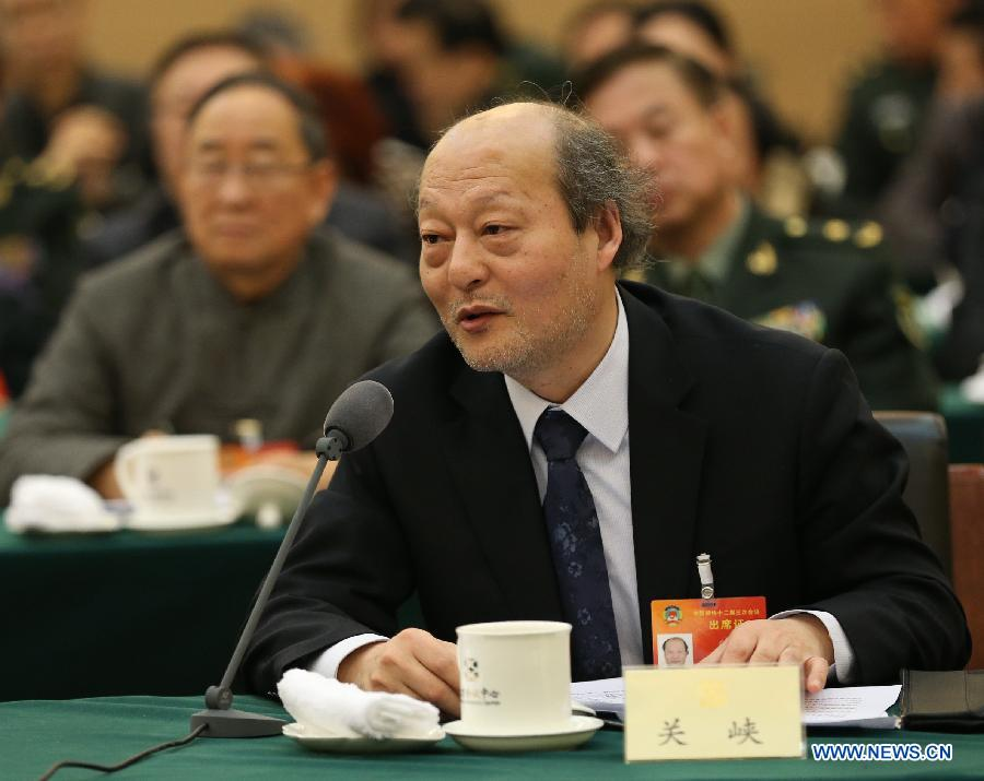 Guan Xia, a member of the 12th National Committee of the Chinese People's Political Consultative Conference (CPPCC), explains his idea of promoting cultural development during a panel discussion for the third session of the 12th CPPCC National Committee in Beijing, capital of China, March 7, 2015. (Xinhua/Ma Zhancheng)