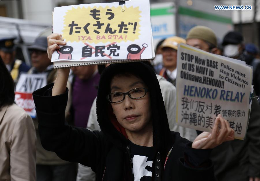 A woman holds a placard during a demonstration to protest against the revision of the pacifist Article 9 of the Japanese Constitution in Tokyo, Japan, April 11, 2015.