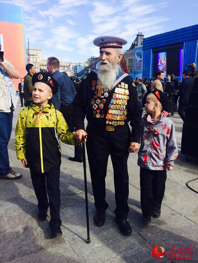 胸前挂满勋章的老兵在曾孙子和曾孙女的搀扶下入场