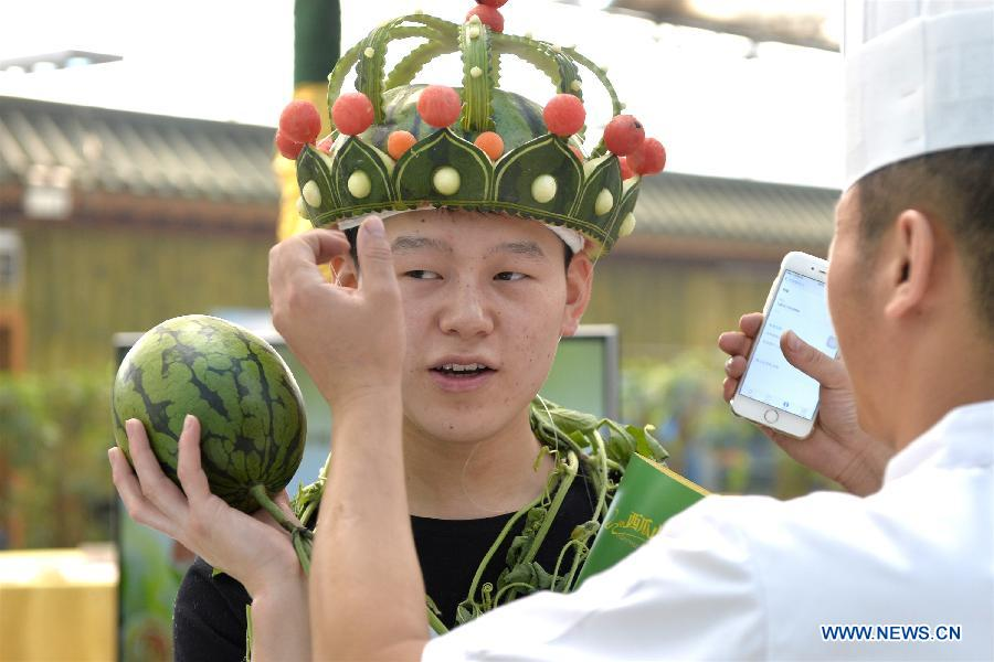 A chef puts his watermelon carving on a man's head during the 27th Daxing Watermelon Festival in Panggezhuang Township of Daxing District of Beijing, capital of China, May 25, 2015. (Xinhua/Gao Jianjun)