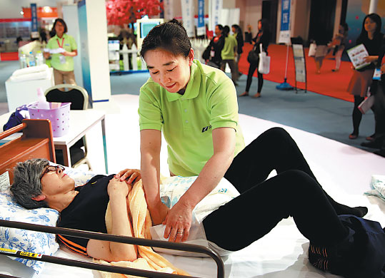 A nursing worker attending the fourth China International Senior Services Expo in Beijing on May 6 shows how she cares for the elderly. (Photo: Pan Xu/Xinhua)