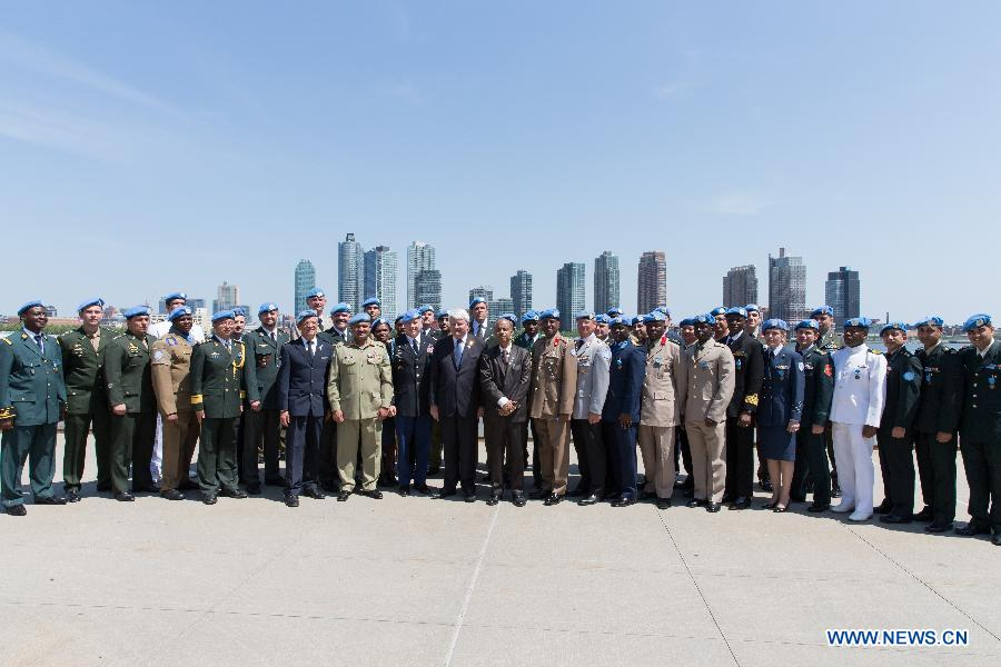 Herve Ladsous (C, front), United Nations Under-Secretary-General for Peacekeeping Operations, poses with military and police personnel awarded the UN medal after a service medal ceremony on International Day of UN Peacekeepers at the UN headquarters in New York, May 29, 2015.