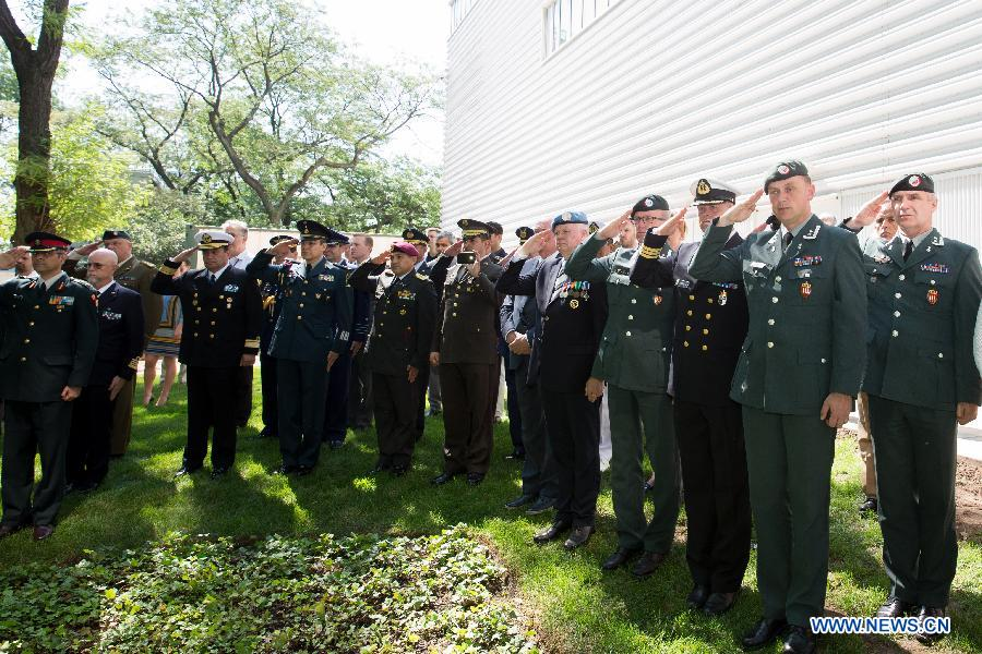 Military personnels salute during a wreath-laying ceremony held on International Day of UN Peacekeepers at the UN headquarters in New York, United States, May 29, 2015.