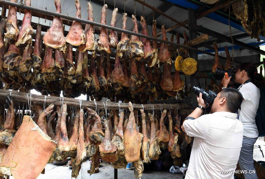 Tourists take photos of cured hams made by a farmer at Anzhao Village of Jingdong County, southwest China's Yunnan Province, June 2, 2015.