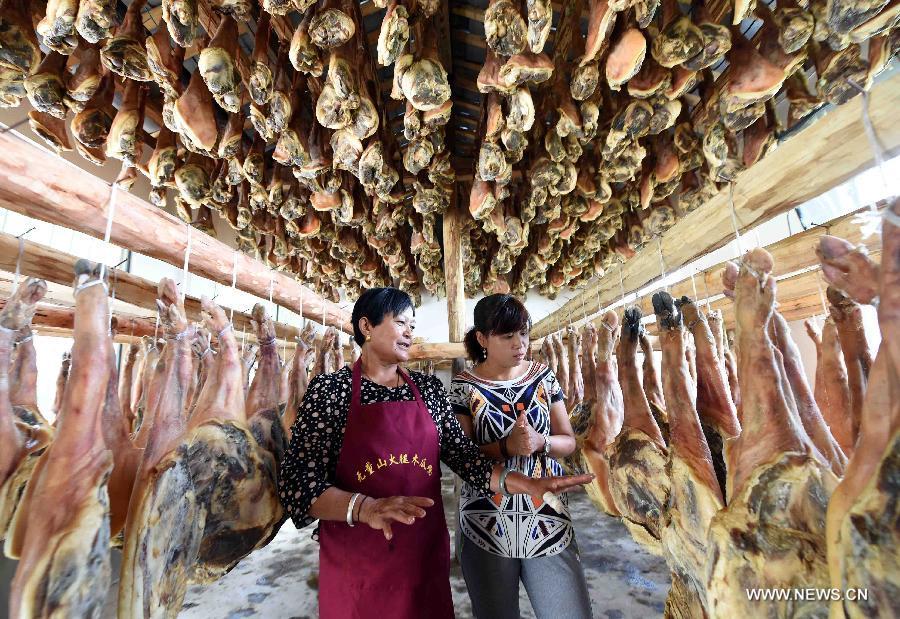 Farmer Shi Wanglian cuts homemade cured hams at Anzhao Village of Jingdong County, southwest China's Yunnan Province, June 2, 2015.