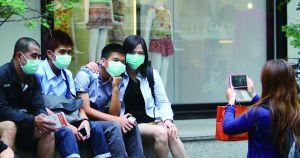 约两万外国游客因MERS取消赴韩旅游,图为戴着口罩的游客在当地合影。