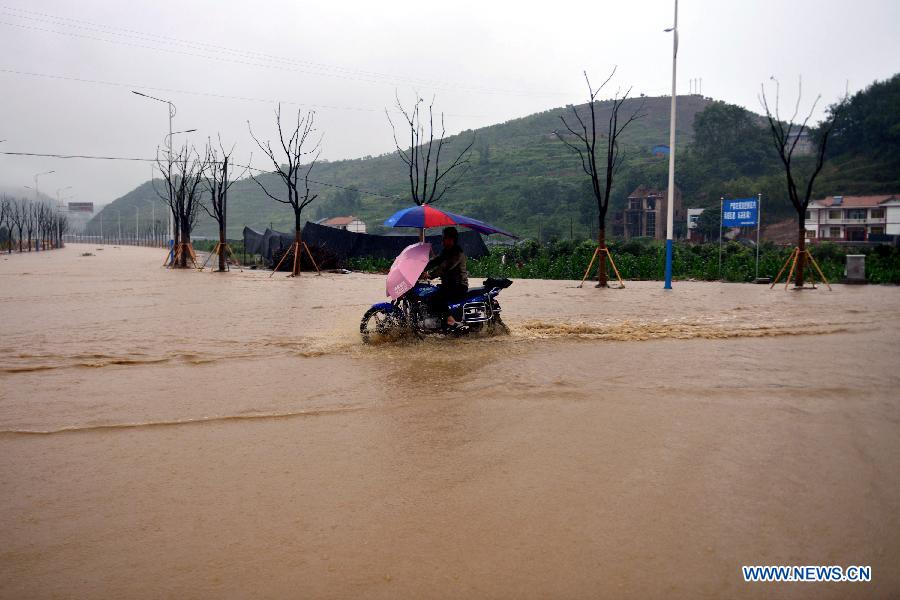 A villager rides on a road submerged by flood water in Tianba Village, Yuqing County, Zunyi City of southwest China's Guizhou Province, June 10, 2015.