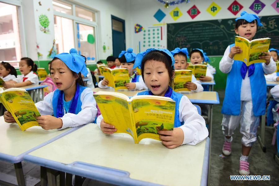 Pupils wearing traditional costumes read classic poetry in an event to learn Duanwu customs at Cuitingyuan Elementary School in Hefei, capital of east China's Anhui Province, June 16, 2015.