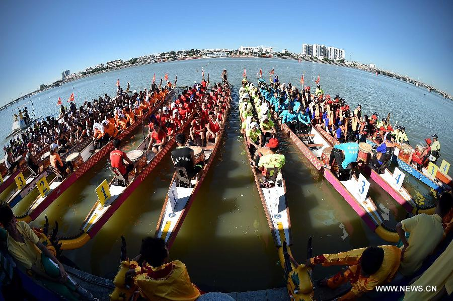 Participants wait for the start of a dragon boat competition in Chengmai, a county in south China's Hainan Province, on June 18, 2015.
