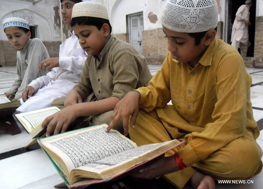 Pakistani Muslim boys read the holy book of Quran during Muslims fasting month of Ramadan at a mosque in northwest Pakistan's Peshawar on June 24, 2015.