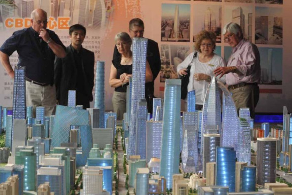 Foreigners look at real estate project models at a central business district (CBD) in Beijing. (File photo)