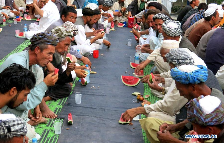 Afghans eat watermelon to break their fast during the holy month of Ramadan at a mosque in Balkh Province, north Afghanistan, July 1, 2015.