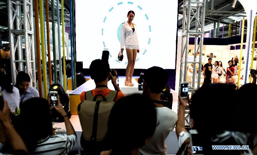 Visitors view a model displaying a creation during the 15th China International Fashion Brand Fair held in Shenzhen, south China, July 9, 2015.
