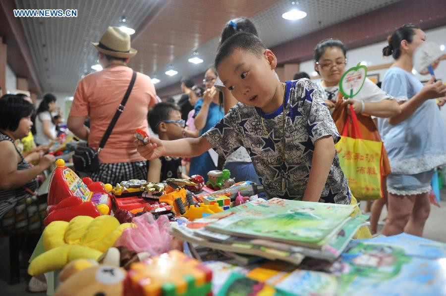 Citizens do their shopping at a flea market when cooling off at a bomb shelter in Chongqing, southwest China, July 9, 2015.