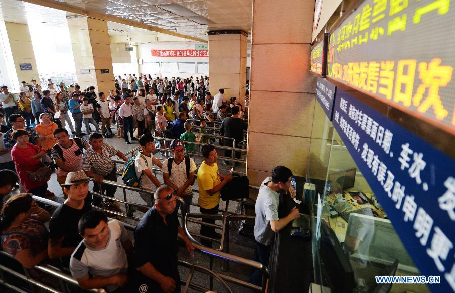 Passengers queue up to buy tickets at Lanzhou Railway Station in Lanzhou, capital of northwest China's Gansu Province, July 13, 2015.