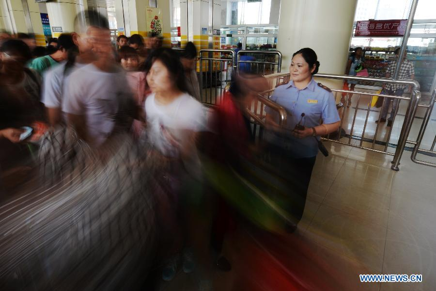 Passengers walk into the station after having their tickets checked at Lanzhou Railway Station in Lanzhou, capital of northwest China's Gansu Province, July 13, 2015.