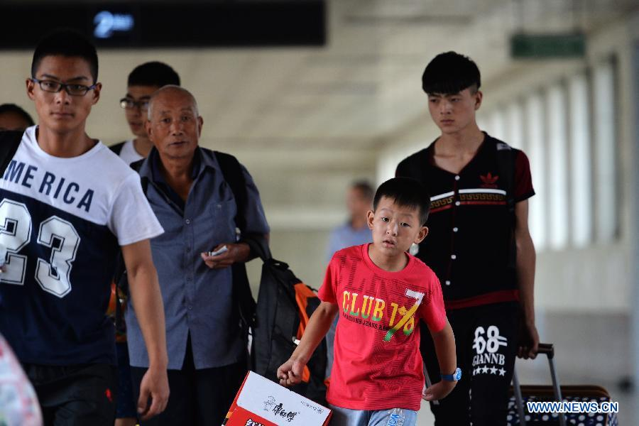 Passengers prepare to board their train at Lanzhou Railway Station in Lanzhou, capital of northwest China's Gansu Province, July 13, 2015.