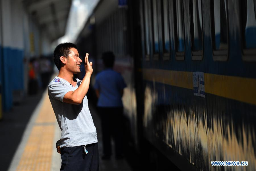 A man waves goodbye on a platform of Lanzhou Railway Station in Lanzhou, capital of northwest China's Gansu Province, July 13, 2015.