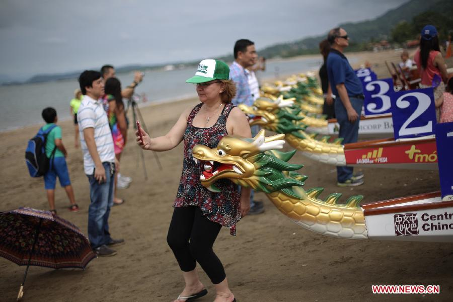 A woman takes a picture with a boat during the first festal event of Chinese dragon boat racing in Panama City, Panama, on July 12, 2015. The event attracted hundreds of people to join in.