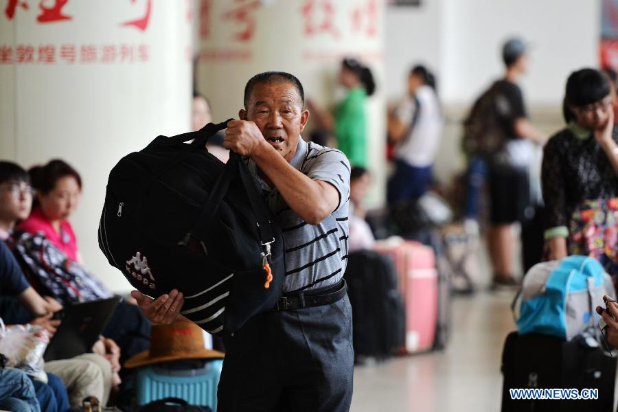 A passenger carrying luggages waits for a train at Lanzhou Railway Station in Lanzhou, capital of northwest China's Gansu Province, July 13, 2015.