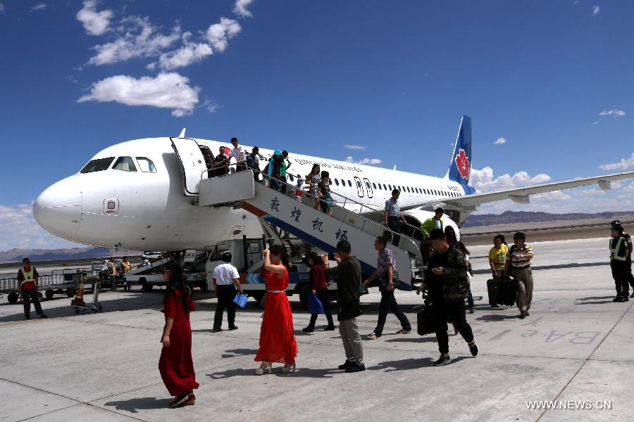 Passengers walk off the plane after the first flight from Qingdao to Dunhuang arrived at Dunhuang Airport in Dunhuang, northwest China's Gansu Province, July 16, 2015.