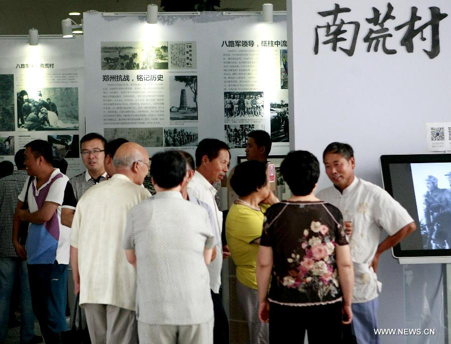 Visitors watch exhibits at an exhibition about the Anti-Japanese War in Zhengzhou, capital of central China's Henan Province, July 16, 2015.