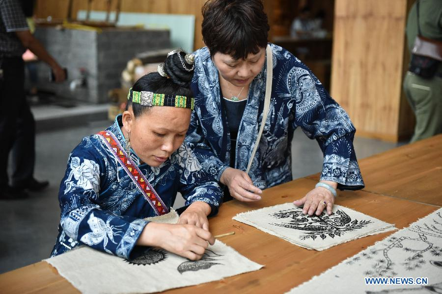 Craftsmen of Miao ethnic group show processes of making batik fabric during a culture expo in Guiyang, capital of southwest China's Guizhou Province, July 24, 2015.