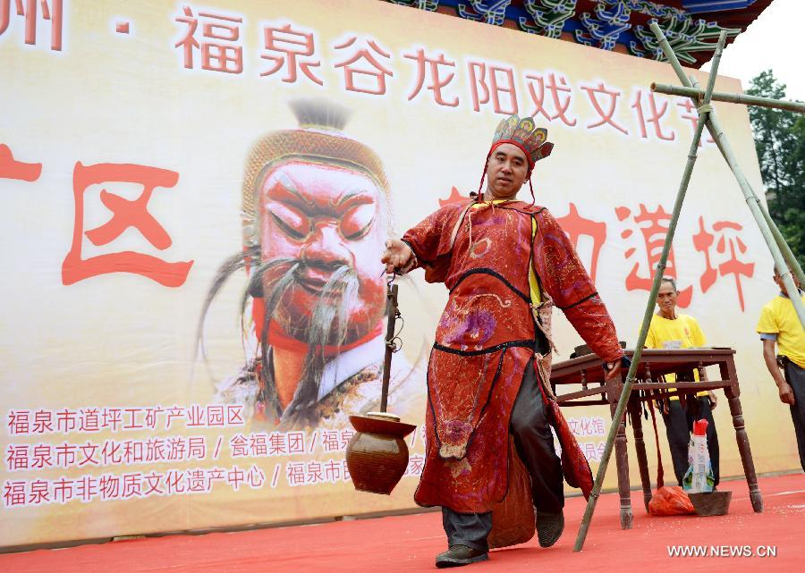 An inheritor of Yang opera performs at a fair in Gulong village, southwest China's Guizhou Province, July 25, 2015. Yang opera, a branch of Nuo opera, is listed in the provincial intangible cultural heritages.(Xinhua/Wu Rubo)