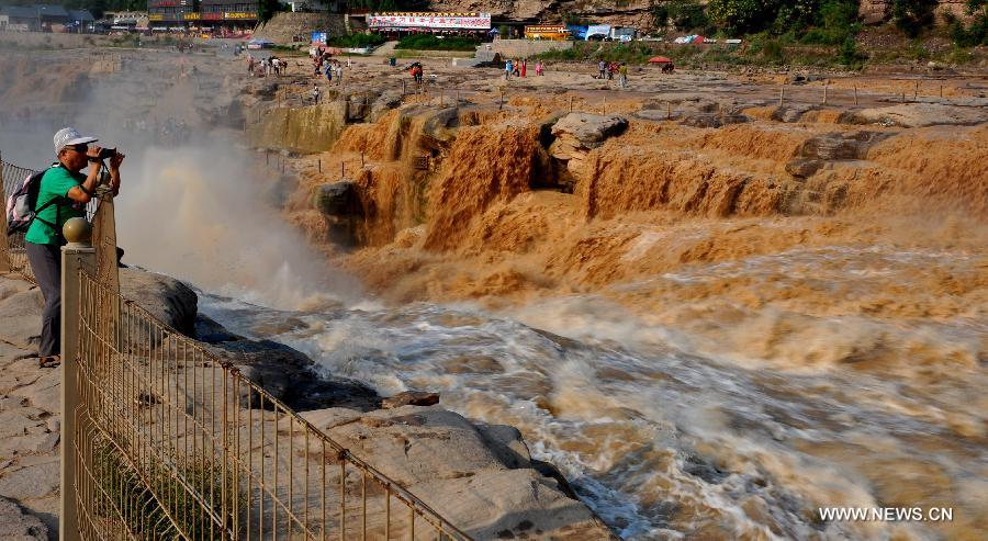 People visit the Hukou waterfall of the Yellow River in Jixian County, north China's Shanxi Province, July 30, 2015. Influenced by heavy rainfalls in the upstream, the half clean and half turbid waterfall became a splendid scenery for sightseeing. (Xinhua/Lyu Guiming)