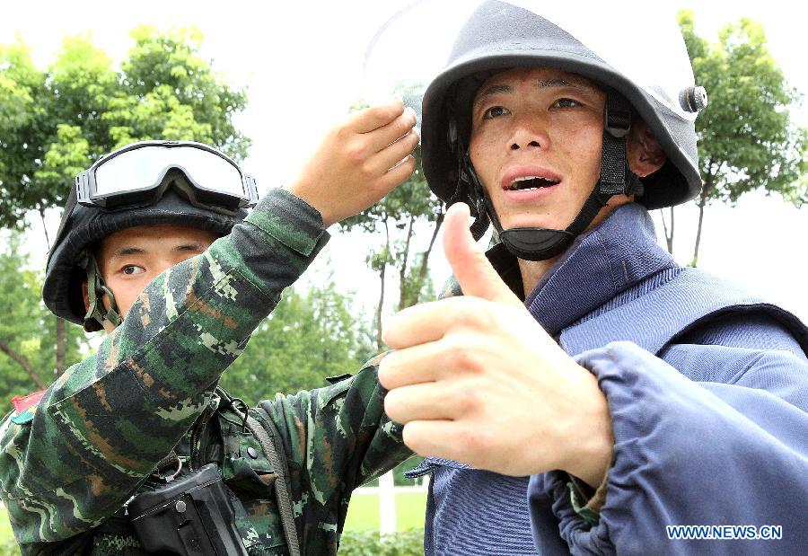 Zhang Yanbiao(R), an Explosive Ordance Disposal(EDO) police, wears a 25-kilogram anti-expolsion suit during a training in east China's Shanghai Municipality, July 30, 2015. EDO police of Shanghai armed police unit continued their training as the heat wave scorched Shanghai. (Xinhua/Chen Fei)