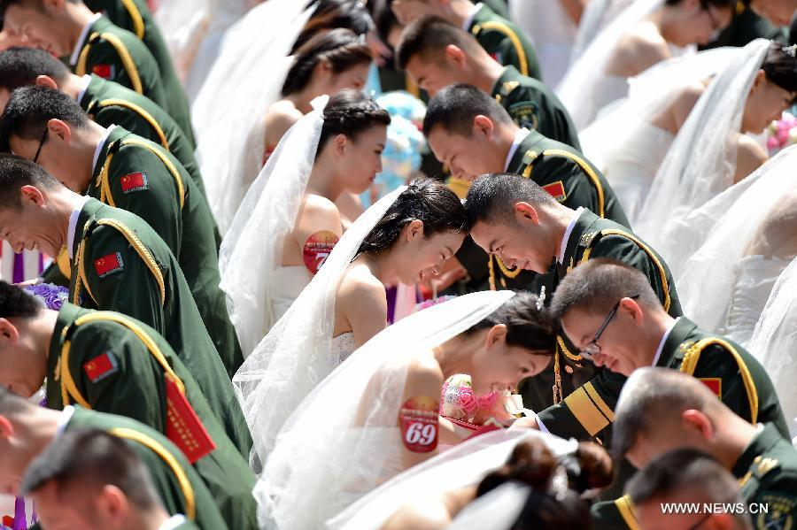 Photo taken on July 31, 2015 shows a group wedding for soldiers in Dongguan City, south China's Guangdong Province. A group wedding was held on Friday for 88 soldiers in Guangdong with the coming of the Army Day and the 88th anniversary of the founding of the Chinese People's Liberation Army, which falls on August 1. (Xinhua/Mao Siqian)