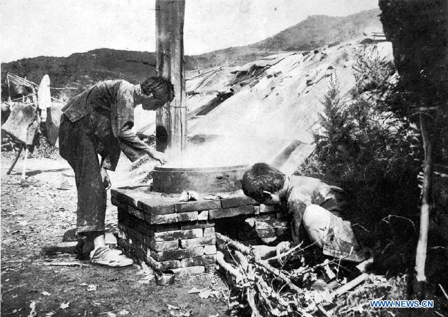 File photo copy shows Chinese forced labors cooking a meal, who were captured by Japanese to build the Fengman hydropower station in Jilin of northeast China after the region was illegally occupied by Japanese invaders in 1931. Japan invaded northeast China in 1931 and conducted a full-scale invasion in 1937. By the end of World War II, millions of Chinese forced laborers had been enslaved by Japanese invaders to toil under harsh conditions at mines and factories in northeast China and Japan. Those laborers were under close watch and suffered inhumane treatment. Many of them died from malnutrition, illness, physical abuse and plain murder. (Xinhua)