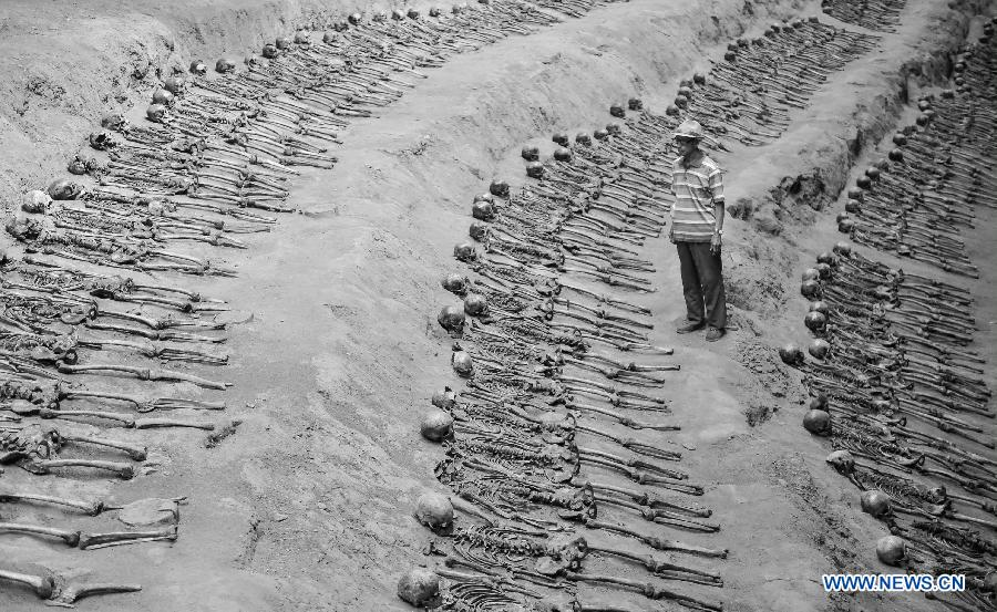 File photo taken on Aug. 28, 2014 shows Sun Yuanxin, who is a surviving forced miner working for Japan during the World War II, looking at the remains of forced miners at a museum of Liaoyuan miners' tomb during Japanese occupation in Liaoyuan, northeast China's Jilin Province. Japan invaded northeast China in 1931 and conducted a full-scale invasion in 1937. By the end of World War II, millions of Chinese forced laborers had been enslaved by Japanese invaders to toil under harsh conditions at mines and factories in northeast China and Japan. Those laborers were under close watch and suffered inhumane treatment. Many of them died from malnutrition, illness, physical abuse and plain murder. (Xinhua/Wang Haofei)
