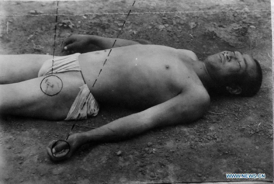 File photo copy taken on Jan. 10, 2014 from the provincial archives of Jilin shows a Chinese forced labor killed by electrocution during Japanese occupation of northeast China. Japan invaded northeast China in 1931 and conducted a full-scale invasion in 1937. By the end of World War II, millions of Chinese forced laborers had been enslaved by Japanese invaders to toil under harsh conditions at mines and factories in northeast China and Japan. Those laborers were under close watch and suffered inhumane treatment. Many of them died from malnutrition, illness, physical abuse and plain murder. (Xinhua/Wang Haofei)
