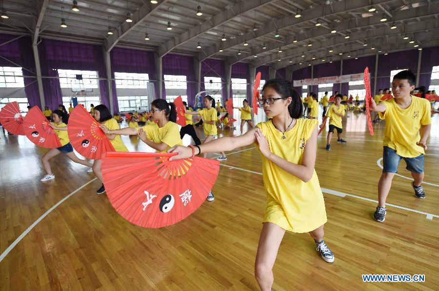 Overseas Chinese youth learn to perform Kung Fu Fan during the 'Chinese Root-Seeking Tour' Summer Camp in Beijing, capital of China, Aug. 7, 2015.