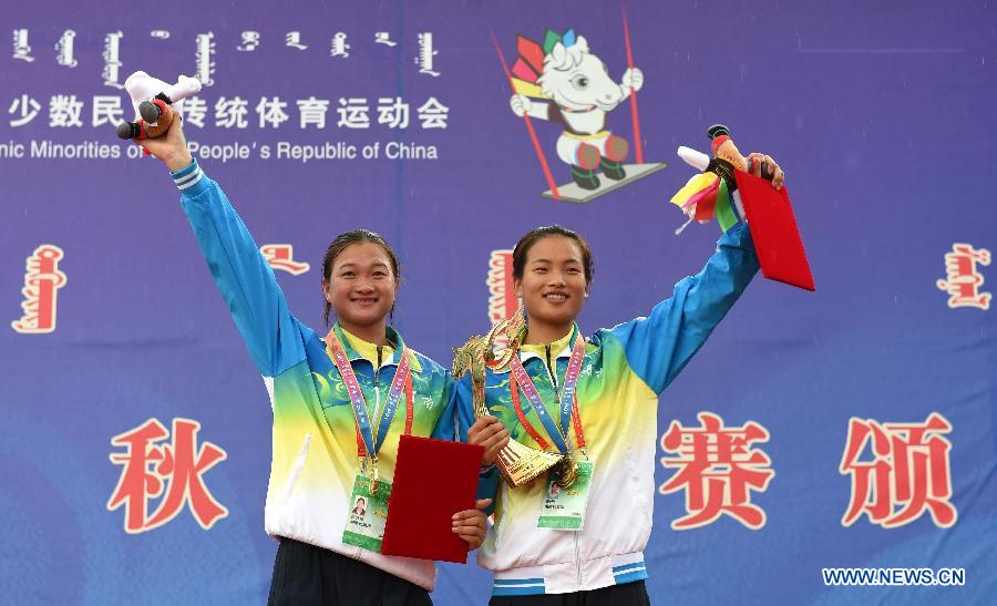 Wu Anzhen (R) and Fei Qianhong from central China's Hunan Province wave to the audience at an awarding ceremony after winning a doule game of swing during the 10th National Traditional Games of Ethnic Minorities of China in Ordos, north China's Inner Mongolia Autonomous Region, Aug. 10, 2015.