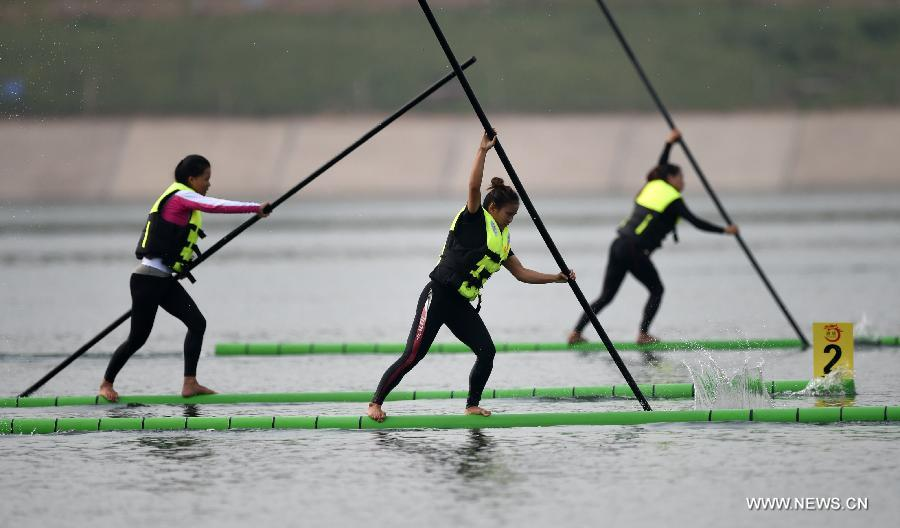 Athletes compete in a women's preliminary match of single bamboo drifting, a specialty in southwest China's Guizhou Province, during the 10th National Traditional Games of Ethnic Minorities of China in Ordos, north China's Inner Mongolia Autonomous Region, Aug. 10, 2015.