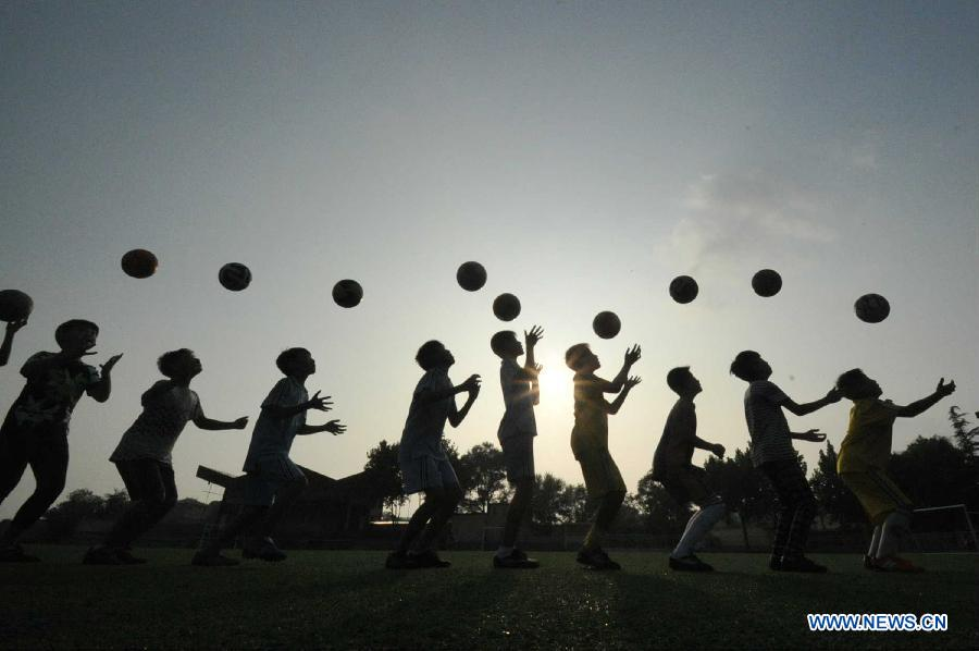Members of a soccer team of Xijie Experimental Elementary School receive training in Xinjiang County of Yuncheng City, north China's Shanxi Province, Aug. 14, 2015.
