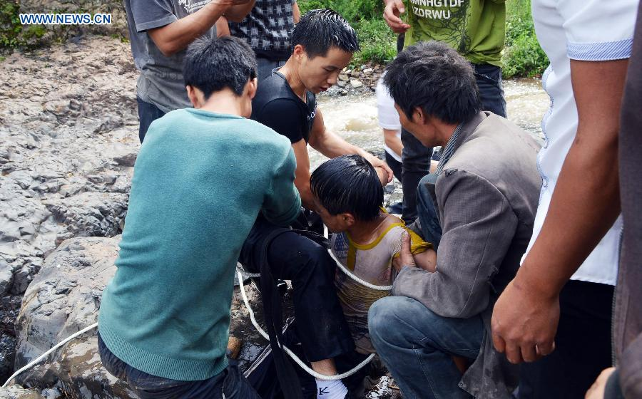 People rescue a boy at Diaoshui Village of Mazha Town in Weining County, southwest China's Guizhou Province, Aug. 16, 2015.