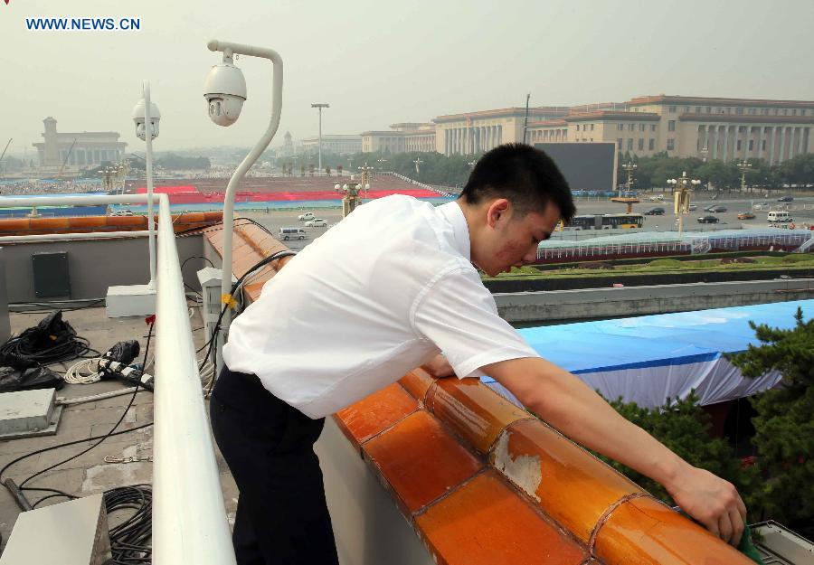 A staff worker cleans glazed tiles at the Tian'anmen Rostrum in Beijing, capital of China, Aug. 17, 2015.